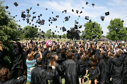 Large group of PHS students tossing their graduation caps in the air