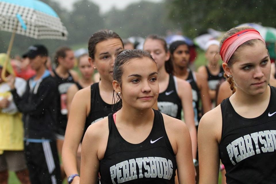 PHS girls cross country runners listening to their coach