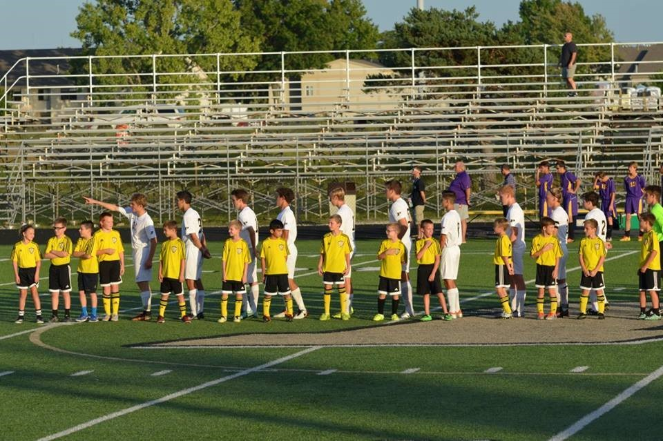 PHS soccer players and youth soccer team standing for the national anthem
