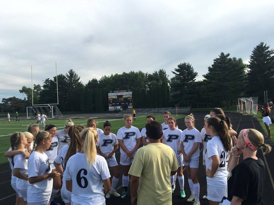 PHS soccer players listening to coach before the game
