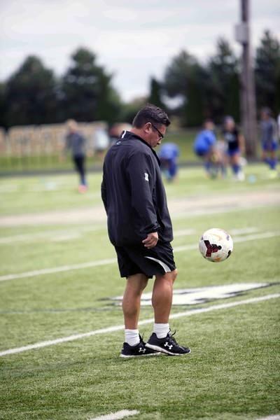 PHS girls soccer coach handling a ball before the game