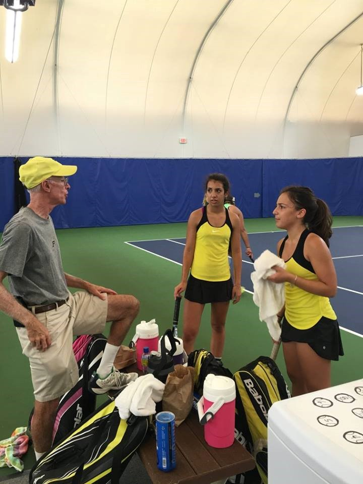PHS tennis players listening to coach
