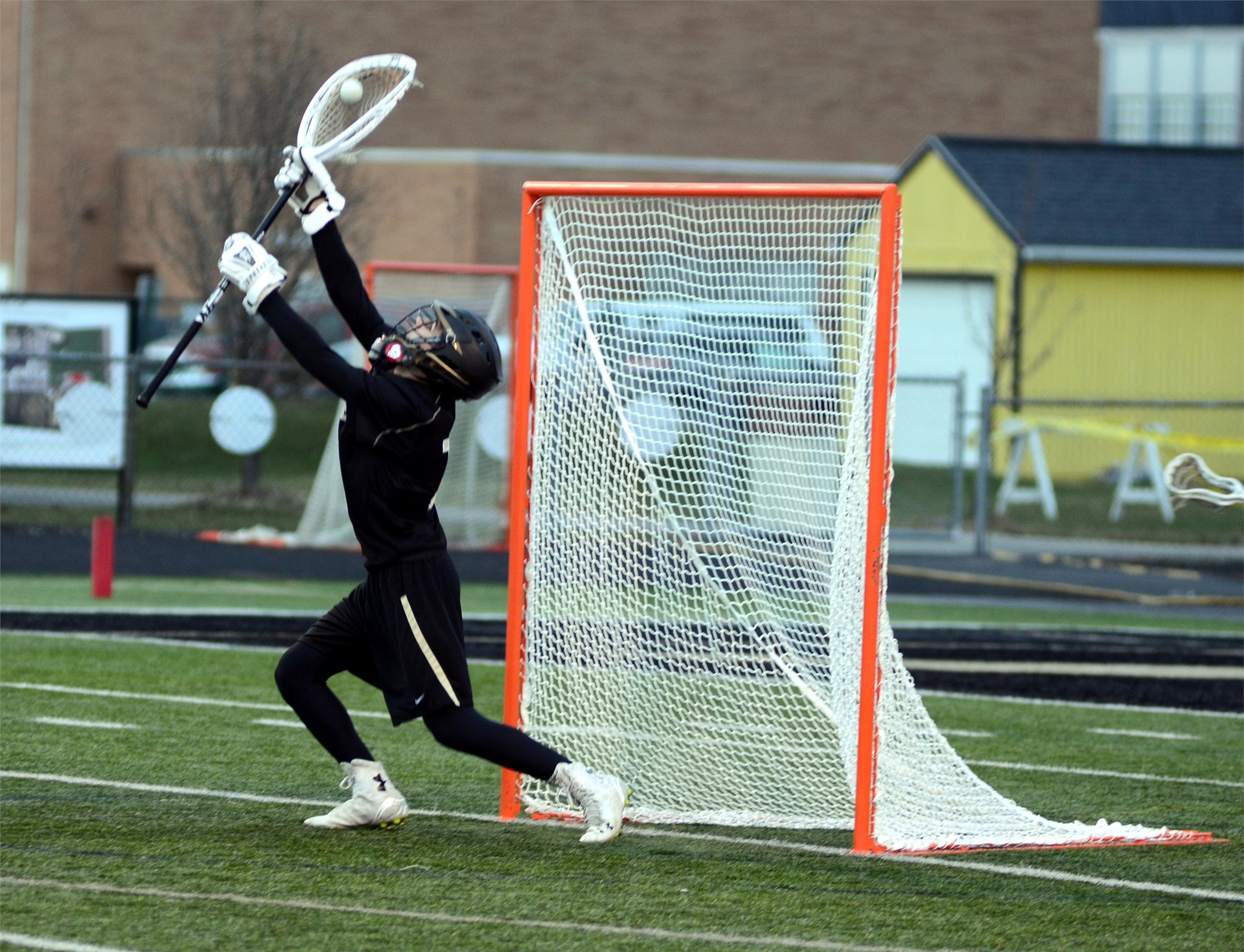 lacrosse player catching a ball in front of the net