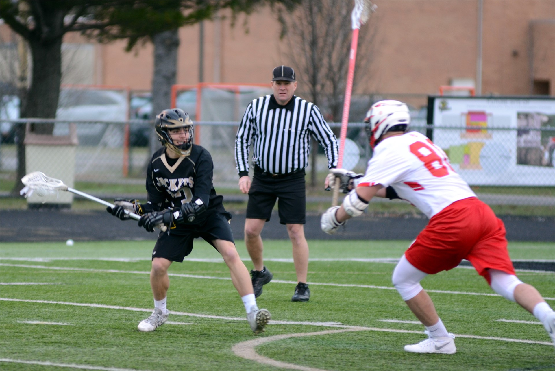 a player from each lacrosse team on the field with a referee in the background