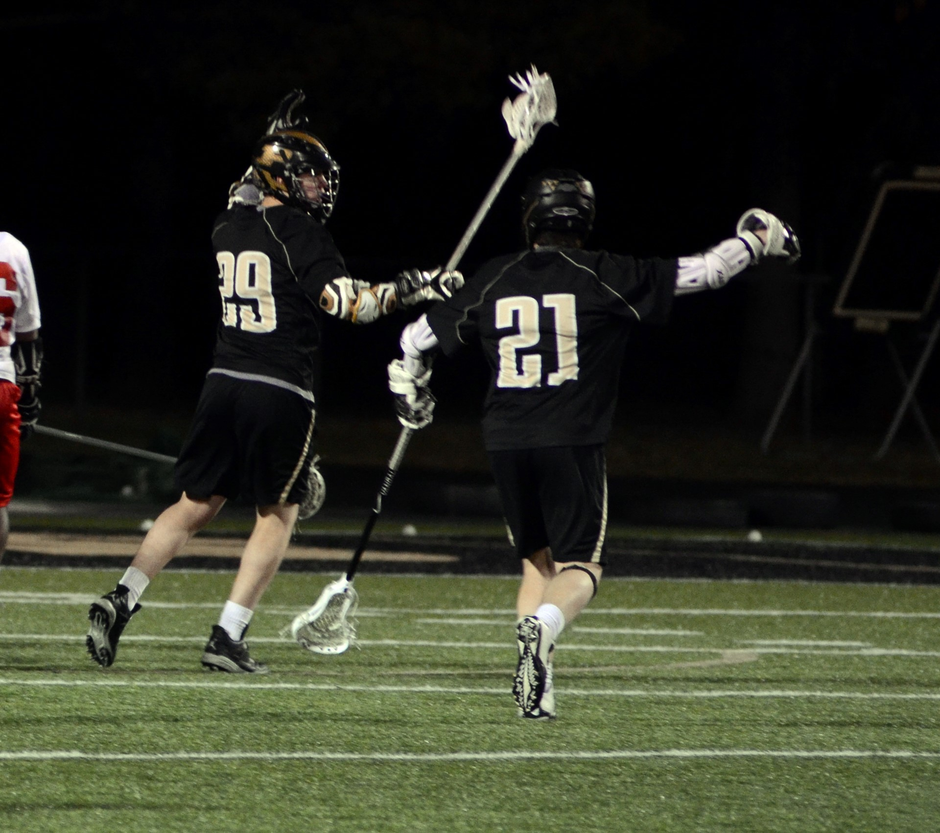 two lacrosse players on the field
