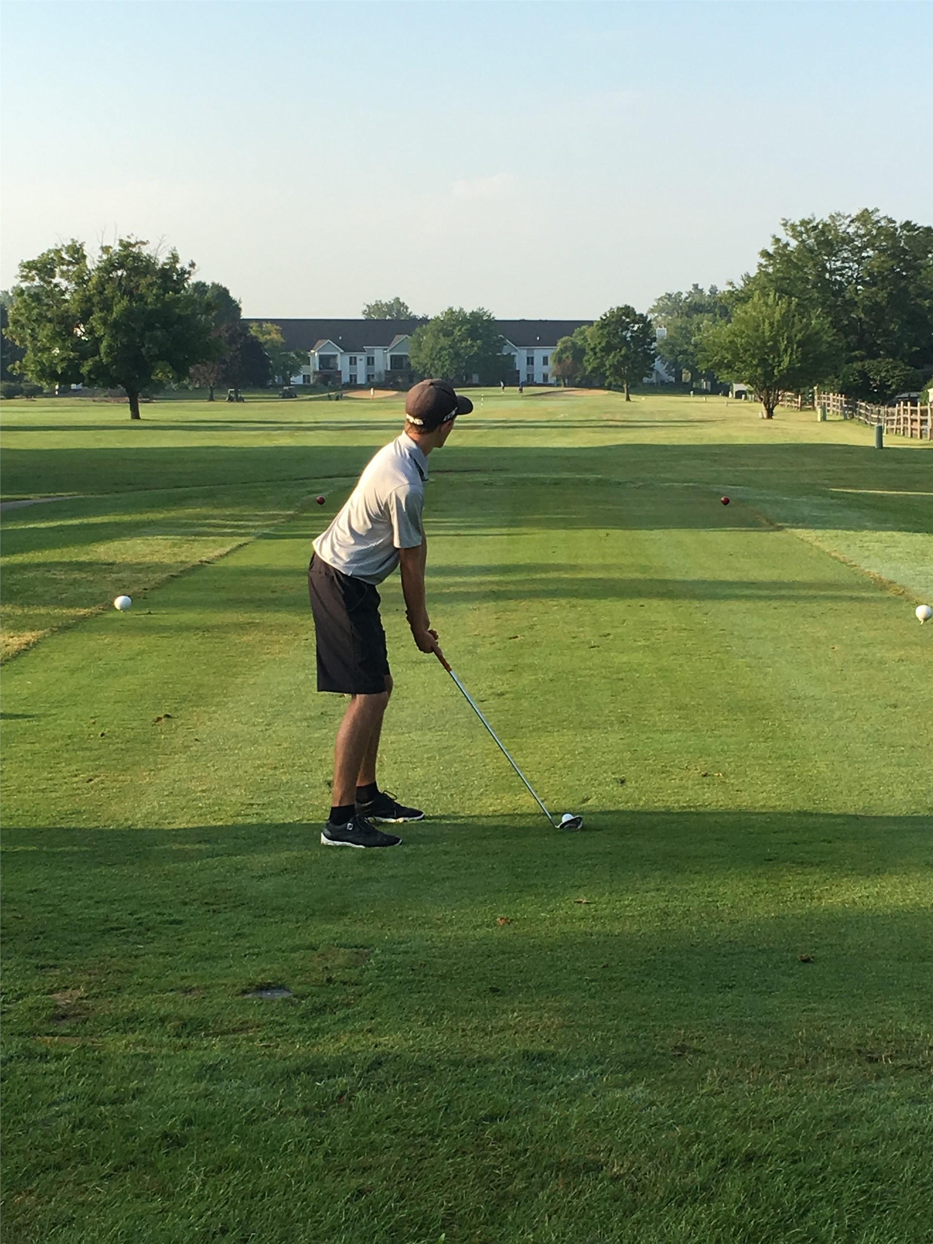PHS student athlete hitting a golf ball