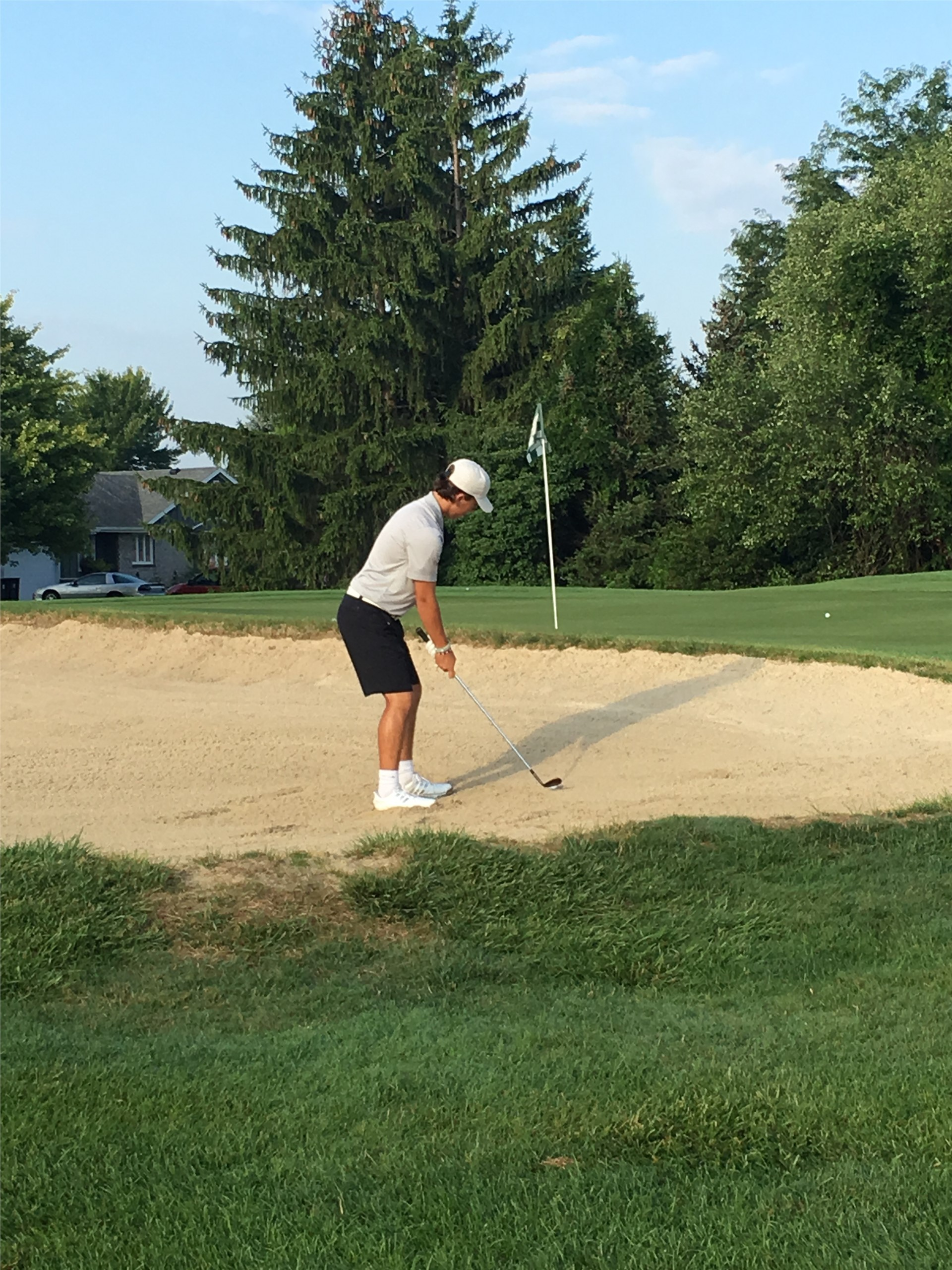 PHS student athlete hitting a golf ball out of the sand