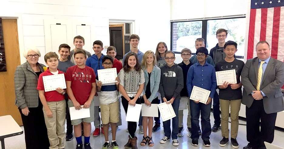 Group photo of smiling students at the board meeting holding up their certificates.