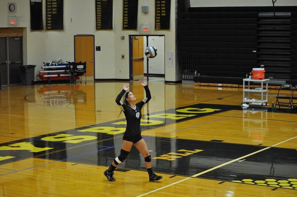 PHS volleyball player serving a volleyball