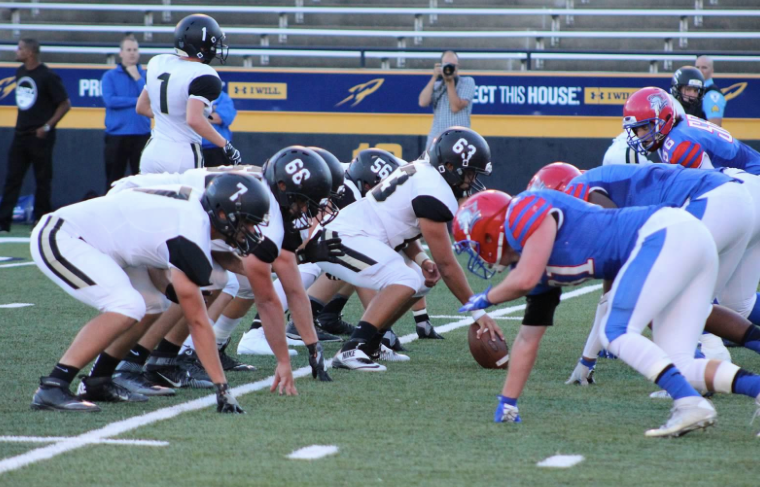 PHS football players at the line of scrimmage