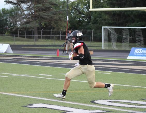 PHS football player running a football