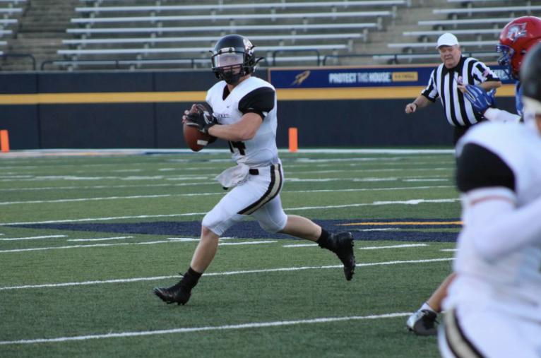 PHS football player throwing a football