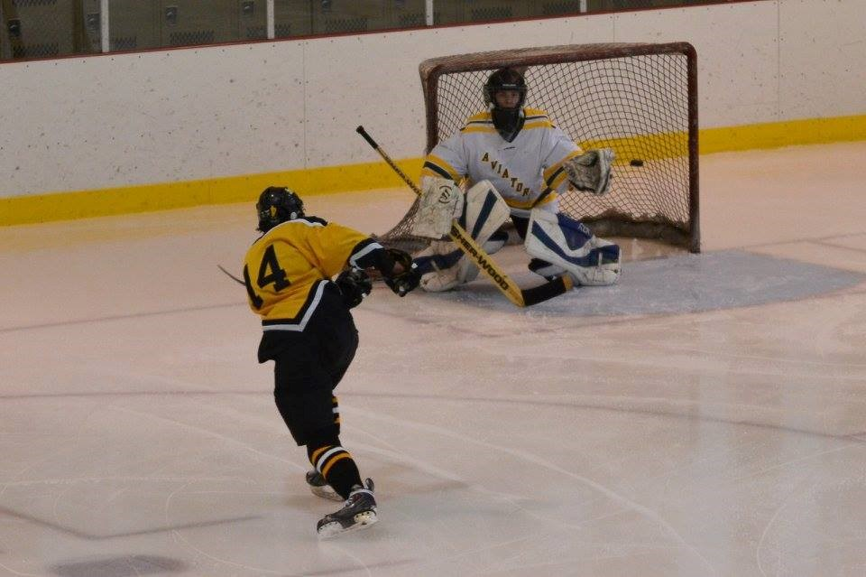 PHS hockey player shooting a puck
