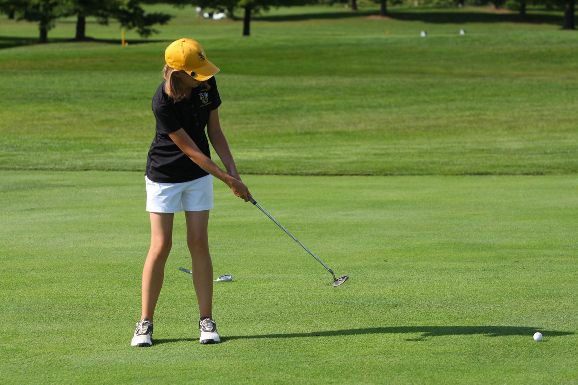 PHS student athlete putting a golf ball