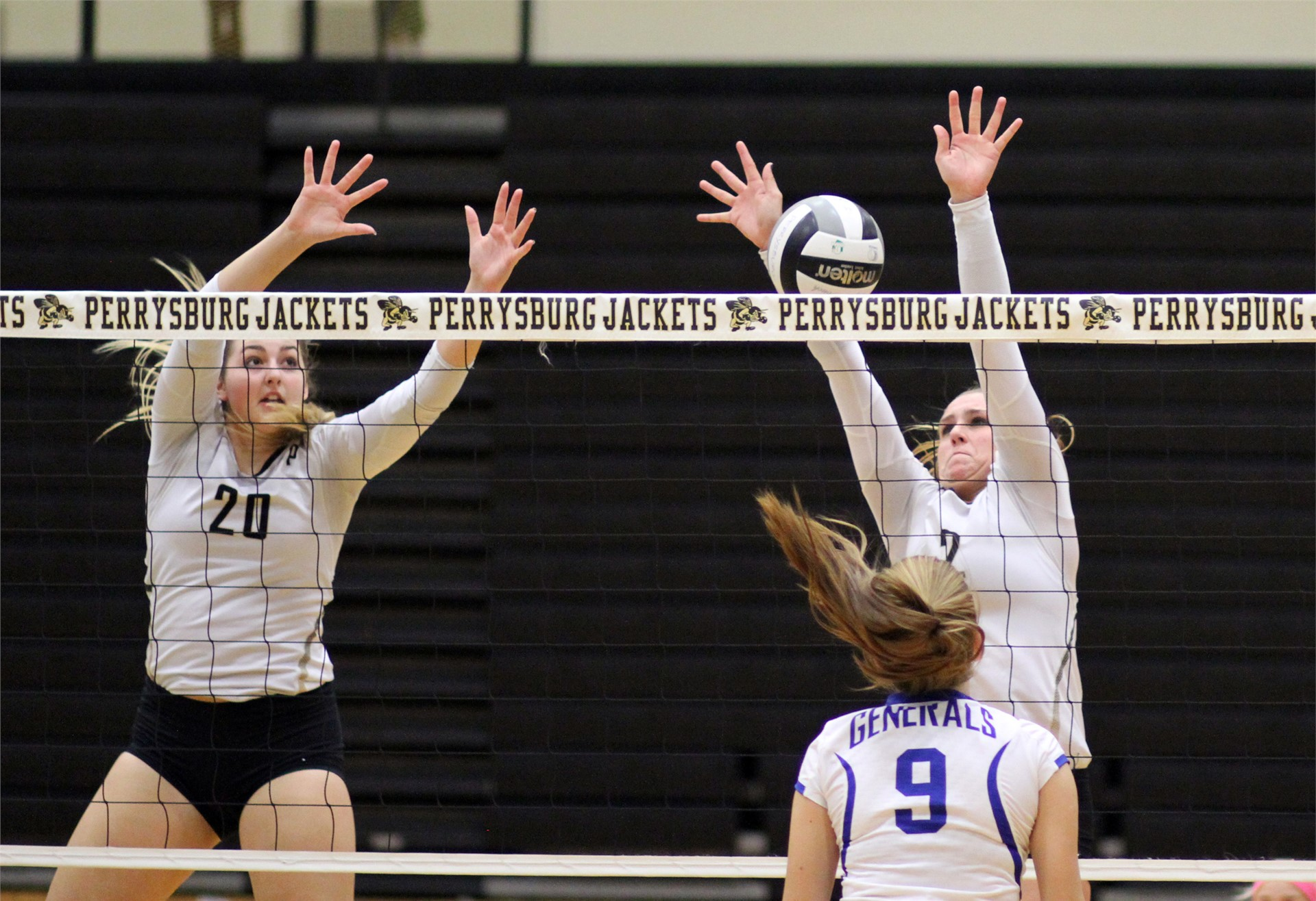 PHS volleyball players attempting to block a shot
