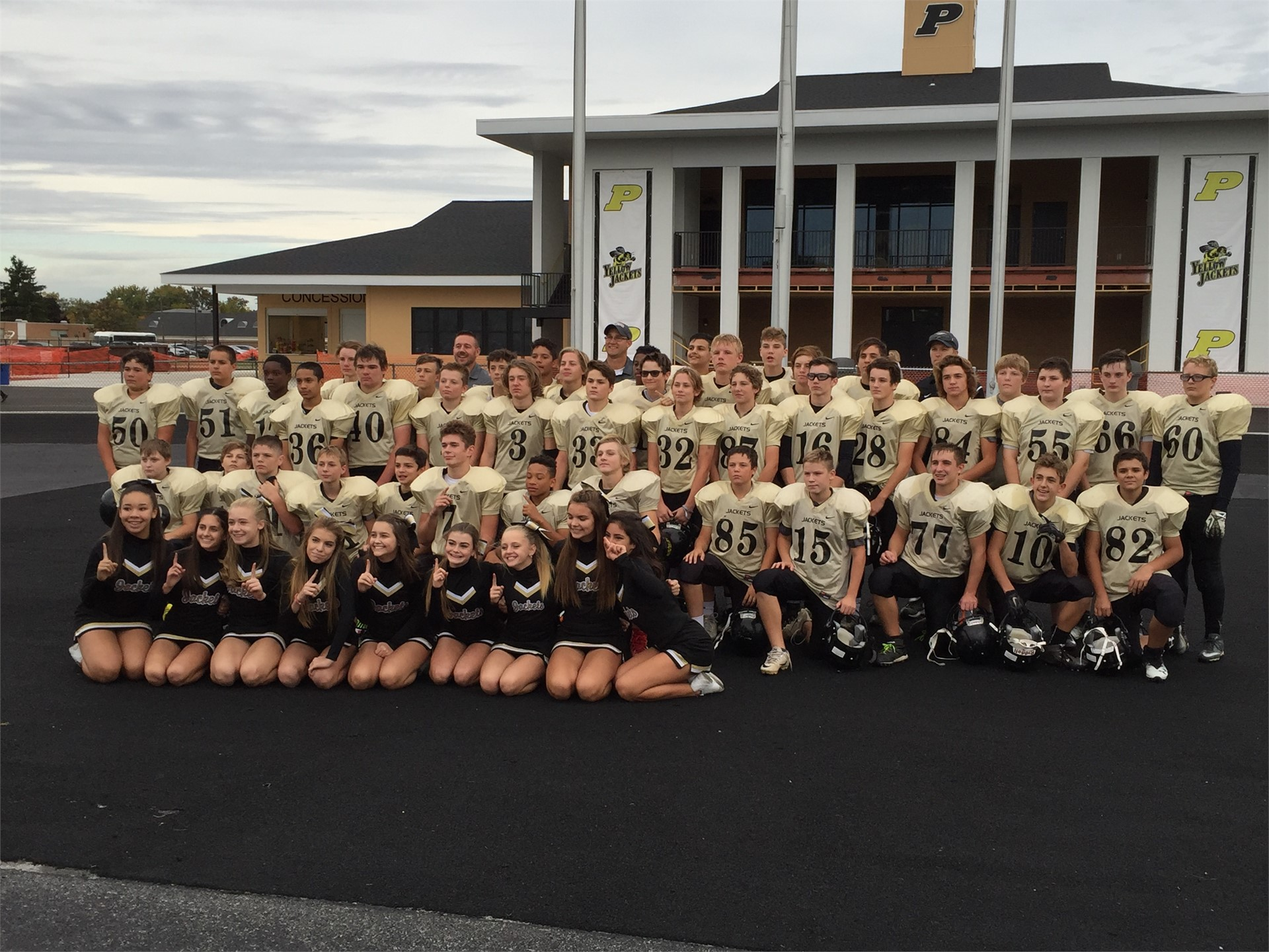 8th Grade NLL Football Champs and cheerleaders pose