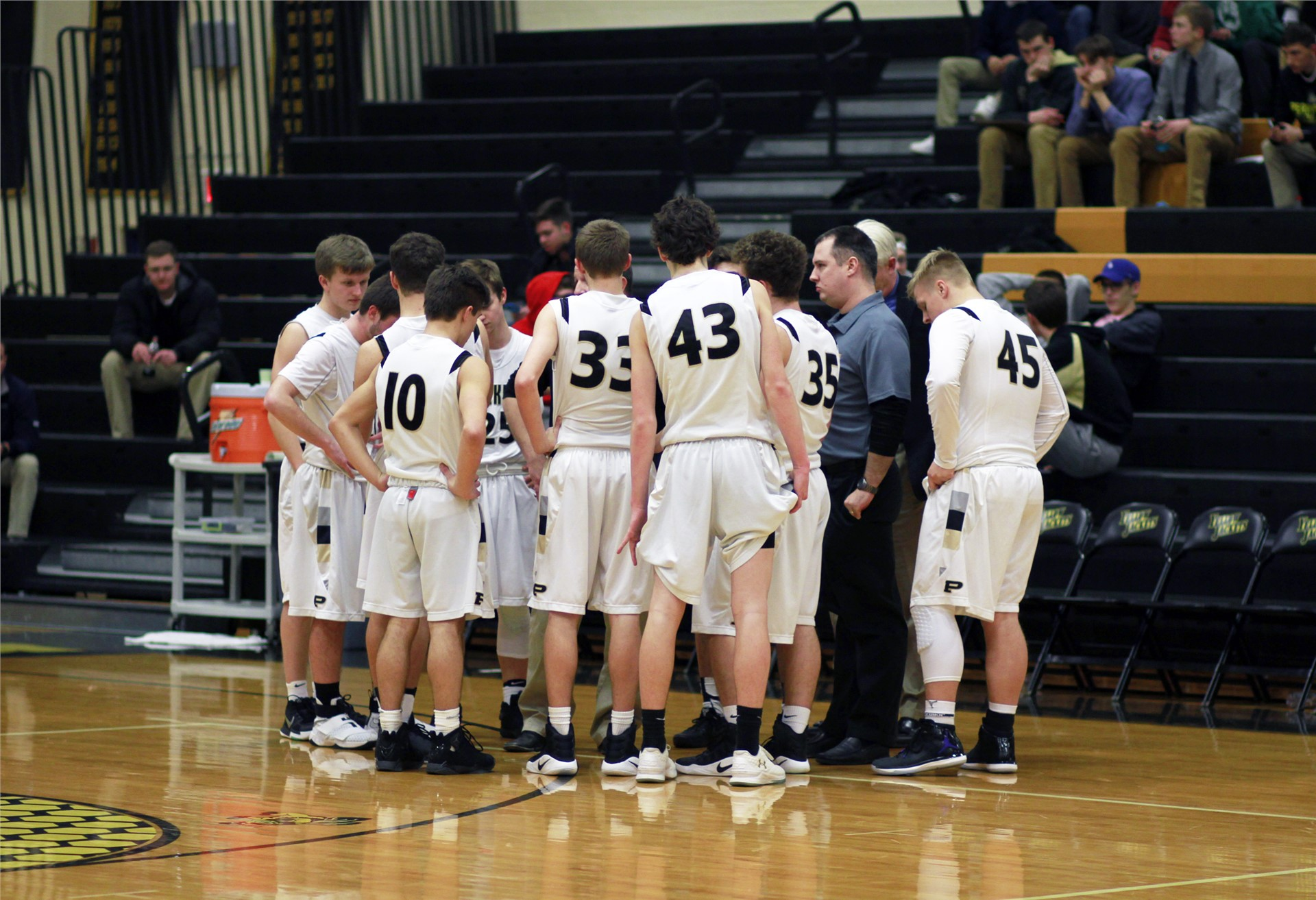 PHS basketball players huddling around coach