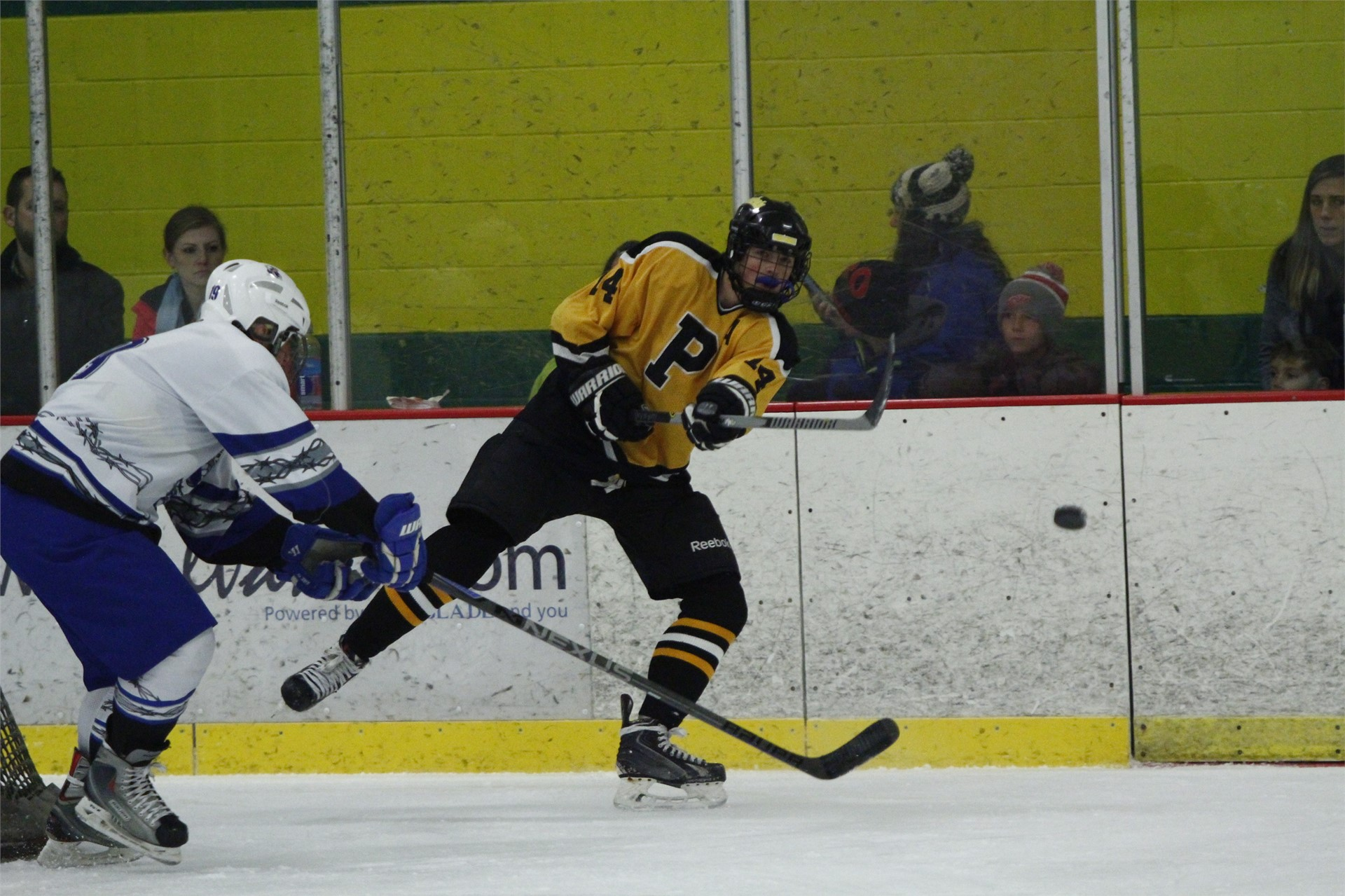 PHS student athlete shooting a puck