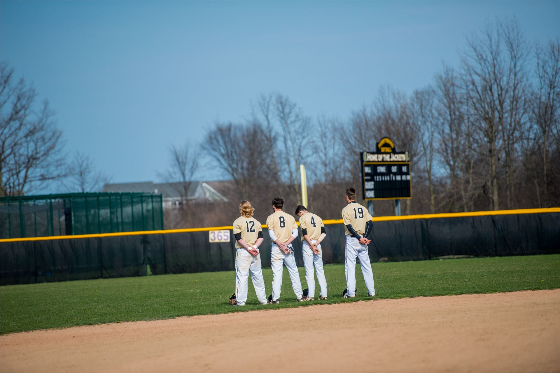 baseball players standing for the national anthem