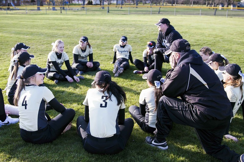 softball players listening to coach talk