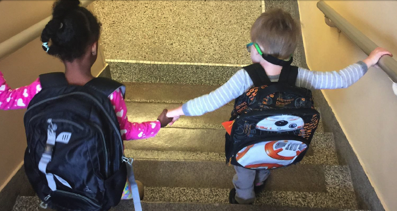 Two preschool students walking down the stairs holding hands