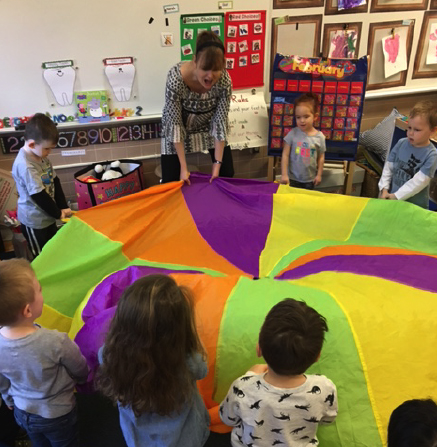 Preschool class with colorful parachute