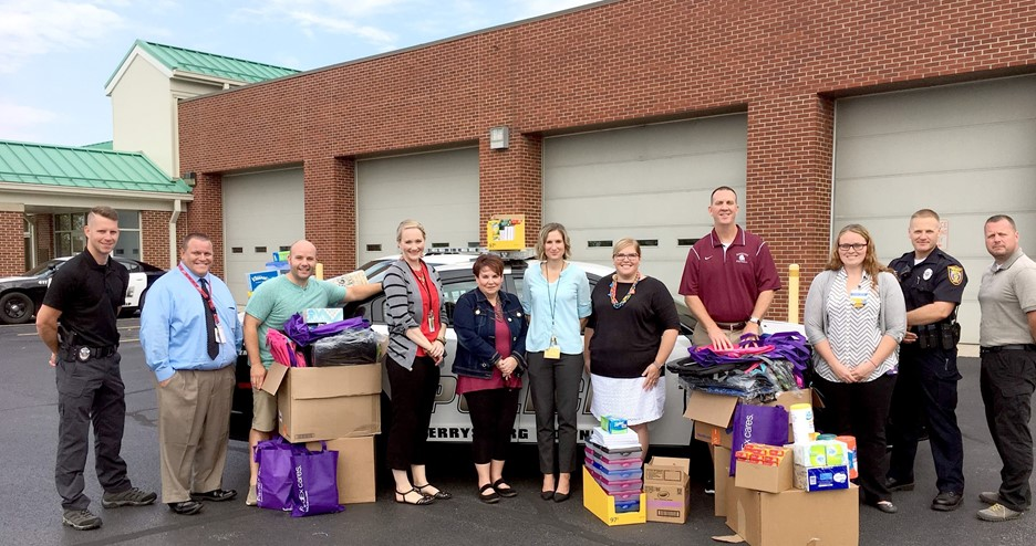 Members of Perrysburg Township Police Department and school district representatives pose with donated supplies in front of police station