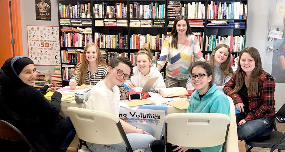 7 students and teacher sitting around a table with bookstore in background