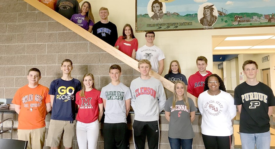 Several students posing and smiling wearing their college shirts