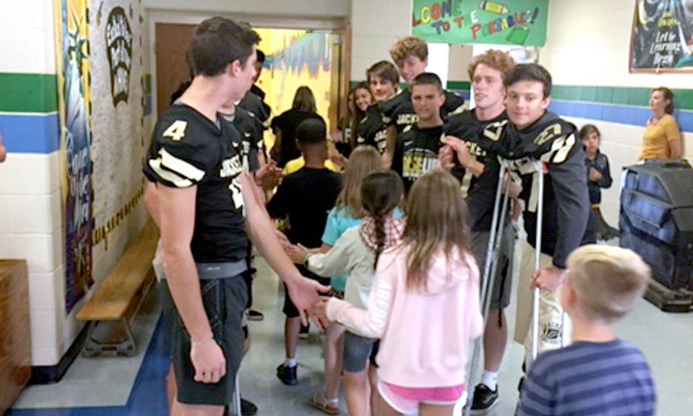 Elementary students shaking hands with members of the high school football team