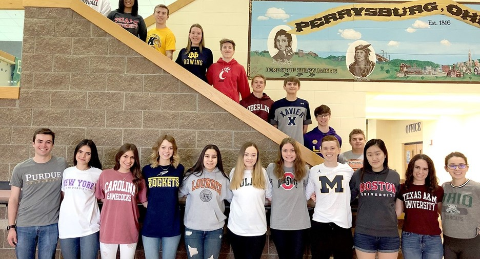Students smiling wearing college shirts