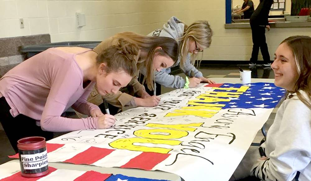 three students signing a fourth student's poster thanking member of the military