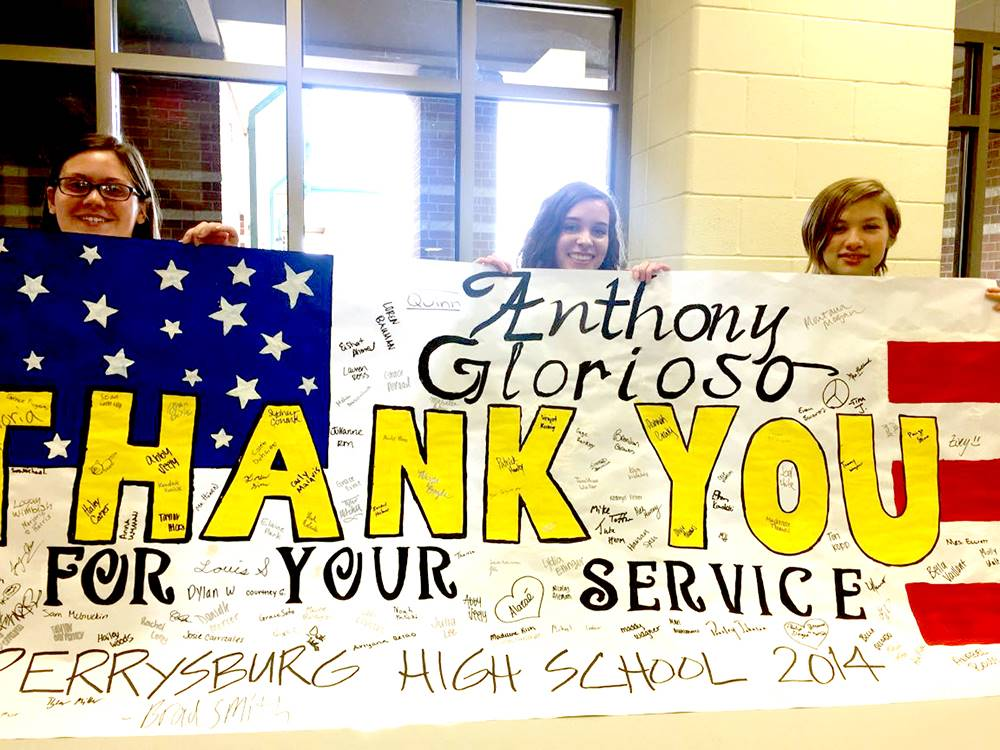 Three students hold banner thanking Anthony Glorioso for his service