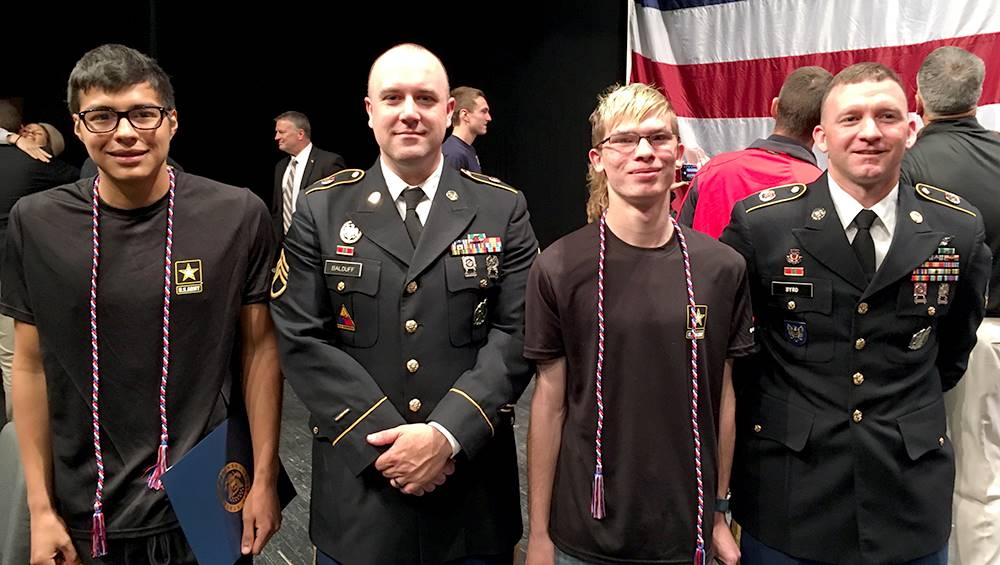 two students and two military representatives at signing day