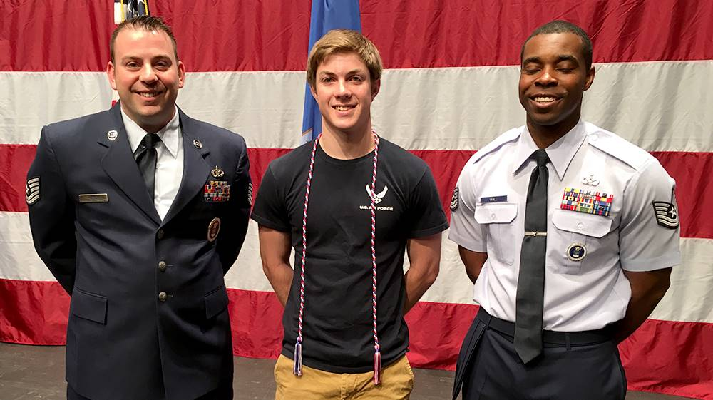 student and two military representatives at signing day
