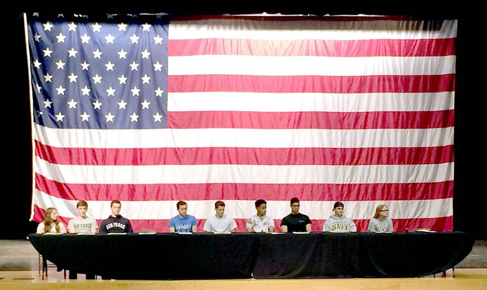 Students on stage in front of a large flag for signing day