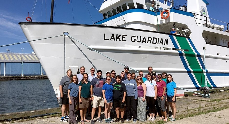 22 people pose in front of a ship named Lake Guardian