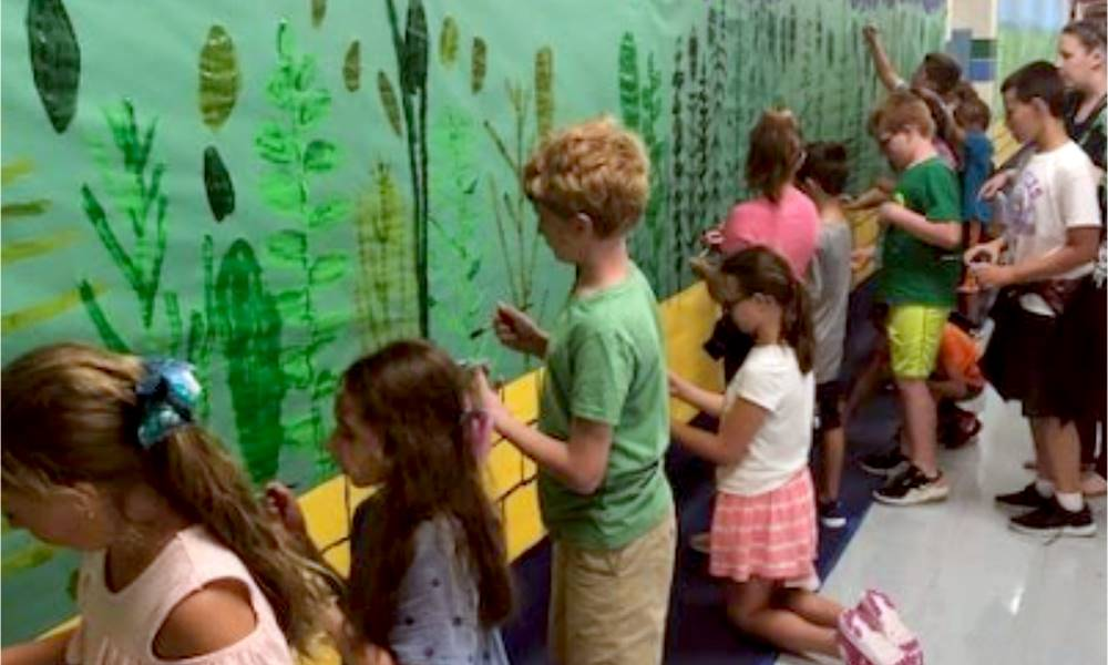 About a dozen students painting a large mural on the wall