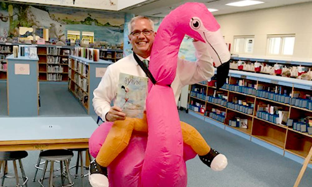 Principal riding a giant flamingo in the library