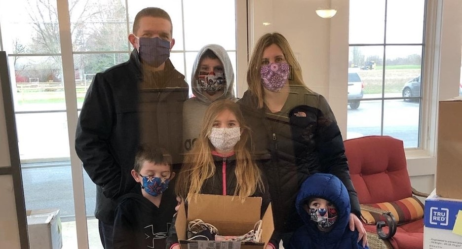 Family wearing masks holding a box of masks to donate