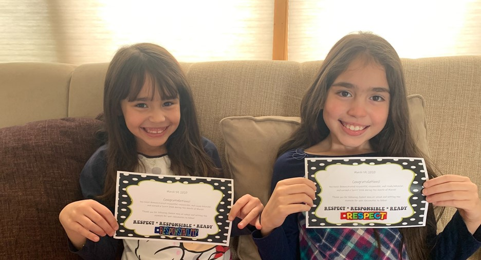two girls holding certificates and smiling