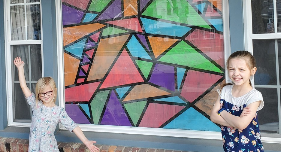 two girls standing in front of geometric artwork in a window