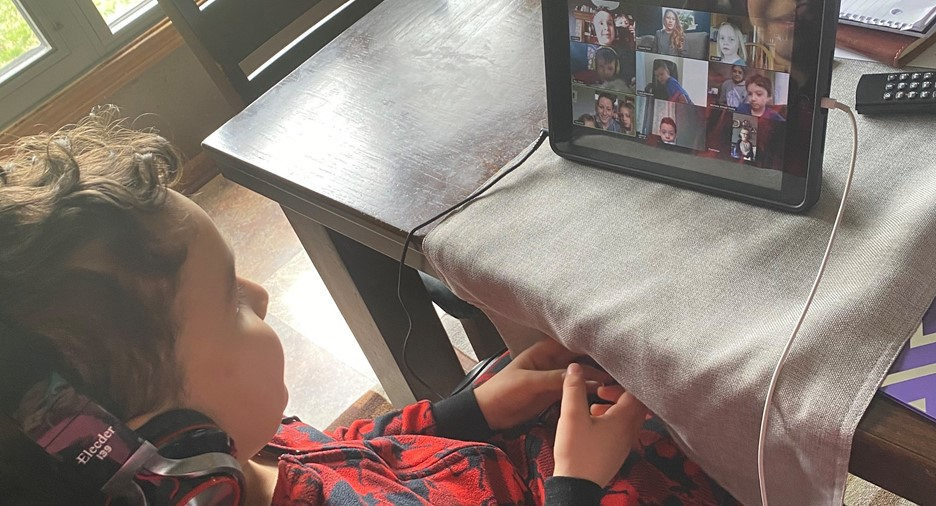 boy wearing headphones and videoconferencing on a tablet