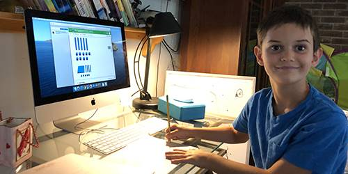 smiling boy sitting at desk with computer