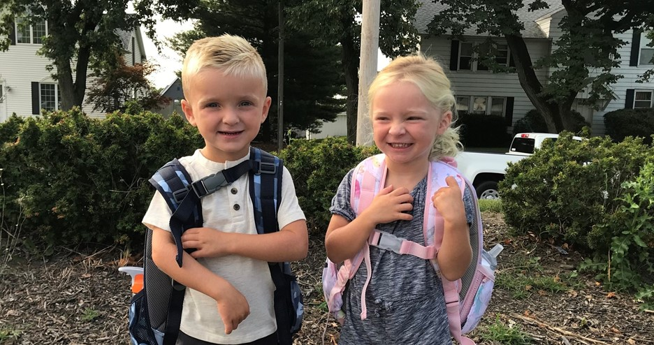 two preschool students smiling outside with backpacks on