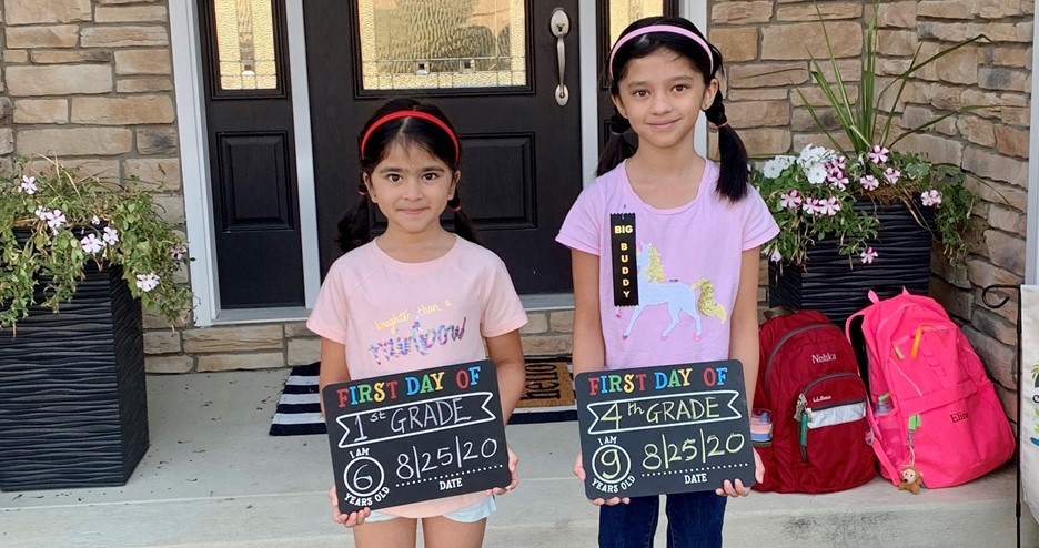 two young students in front of their house holding first day of school signs