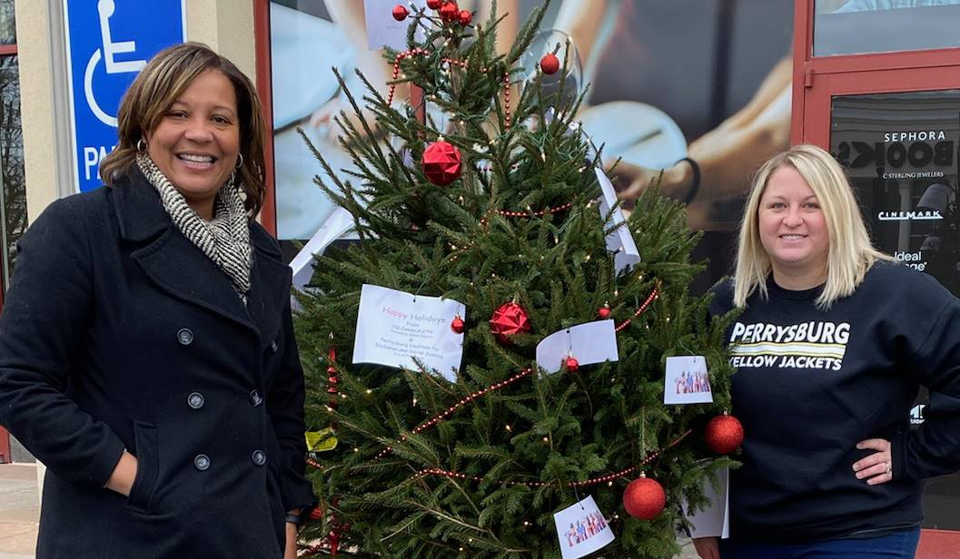 two people smiling by decorated tree