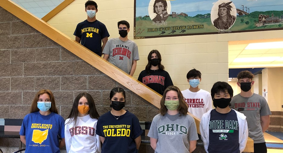 A group of students wearing college shirts