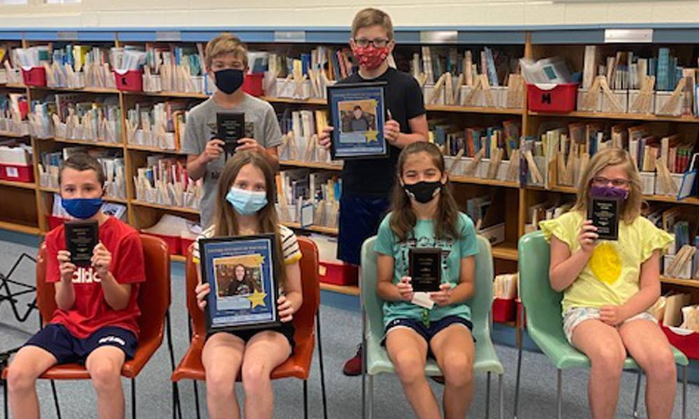 six students holding up books in the library