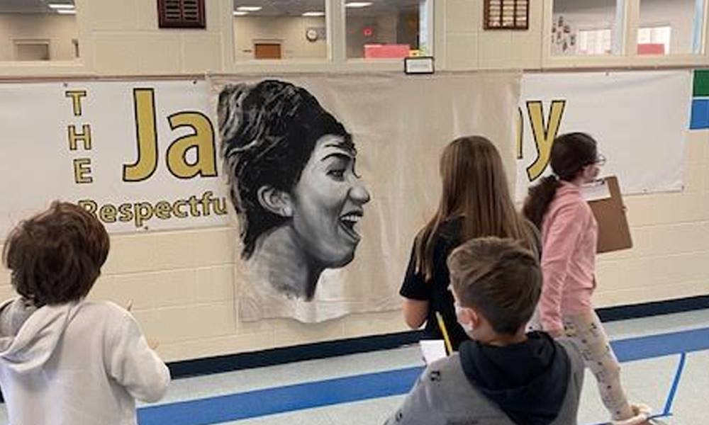 students in hallway looking at a portrait painting